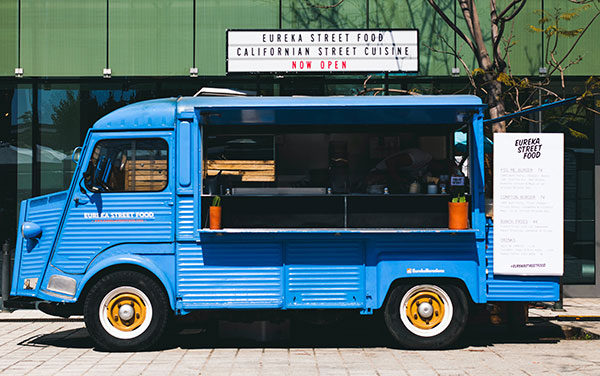 an image of a blue food truck in from of an office building.