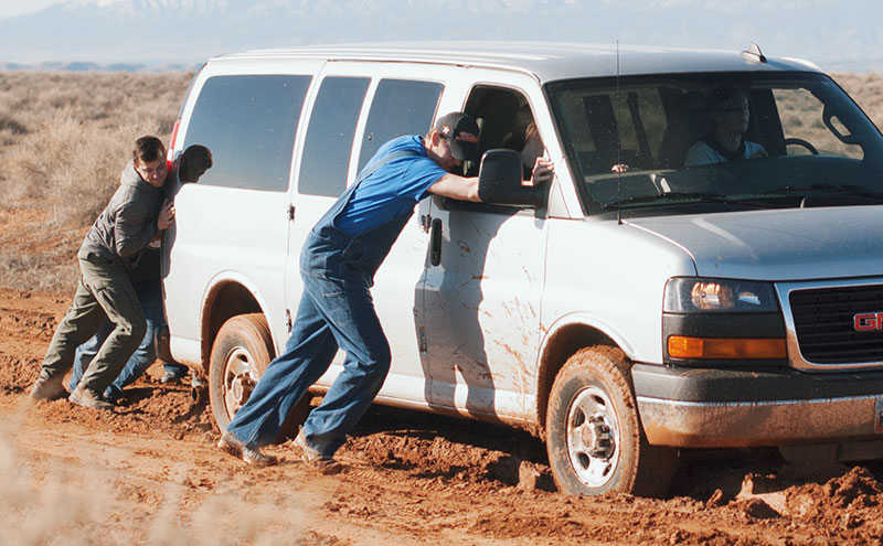 People trying to help a van stuck in a rut.